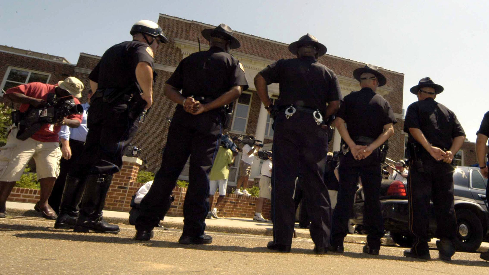 """PHILADELPHIA, MS - Philadelphia police stand guard outside the Neshoba County Courthouse during the trial of Edgar Ray Killen on June 15, 2005 in Philadelphia, Mississippi. Killen is accused in the 1964 slayings of civil rights workers James Chaney, Andrew Goodman and Michael Schwerner in a case that came to be known as """"Mississippi Burning.""""  (Photo by Marianne Todd/Getty Images)"""