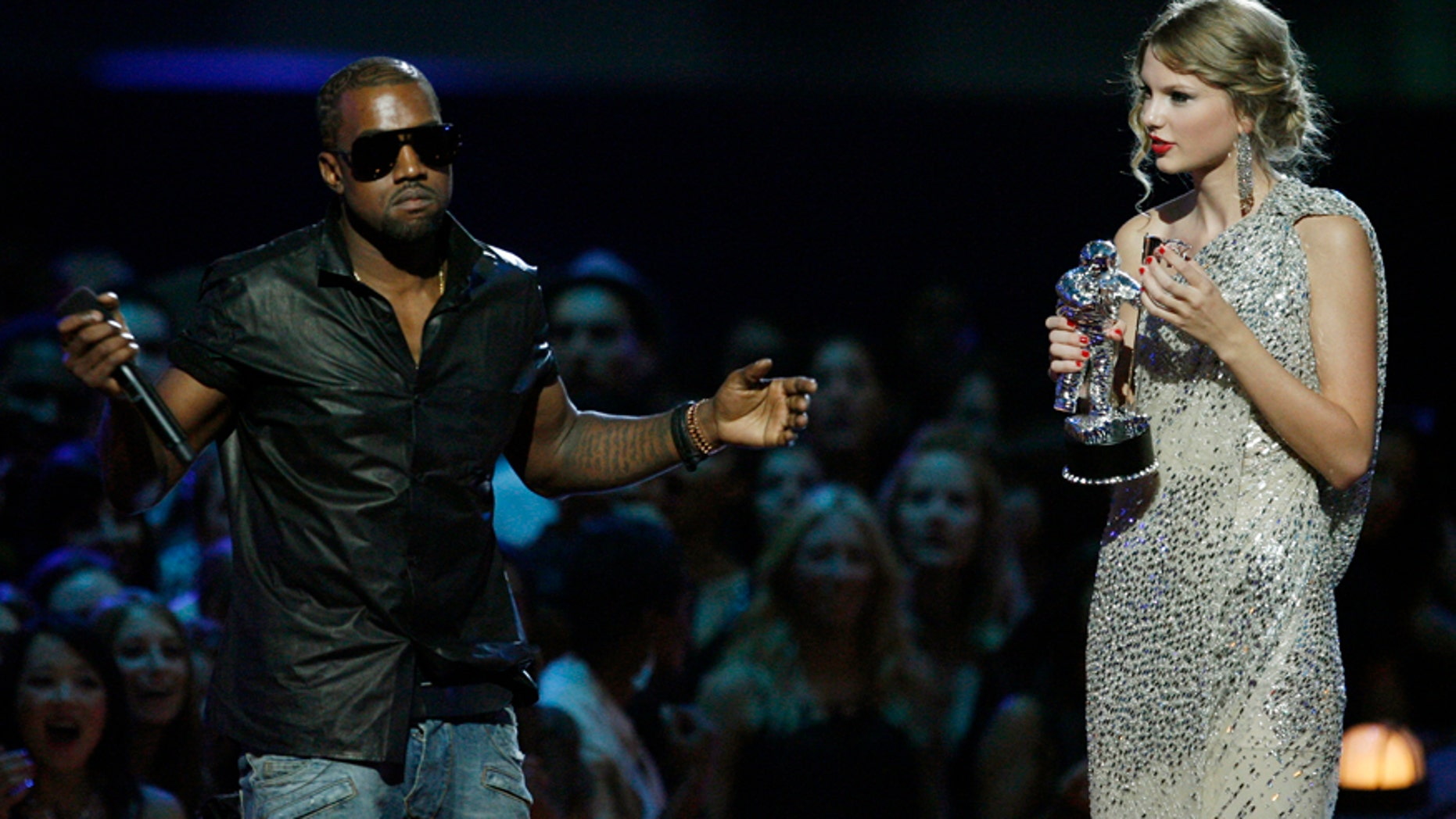 """In this Sept. 13, 2009 file photo, singer Kanye West takes the microphone from singer Taylor Swift as she accepts the """"Best Female Video"""" award during the MTV Video Music Awards in New York. West ranted about how Beyonce was more deserving of the award."""