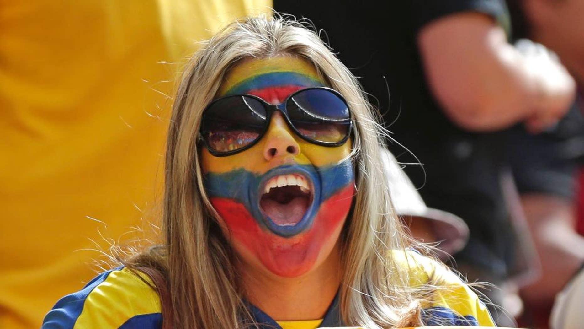 Una hincha ecuatoriana con la cara pintada agita una bandera antes del partido frente a Suiza, por el Grupo E del Mundial, disputado el domingo 15 de junio de 2014, en Brasilia (AP Foto/Marcio José Sánchez)