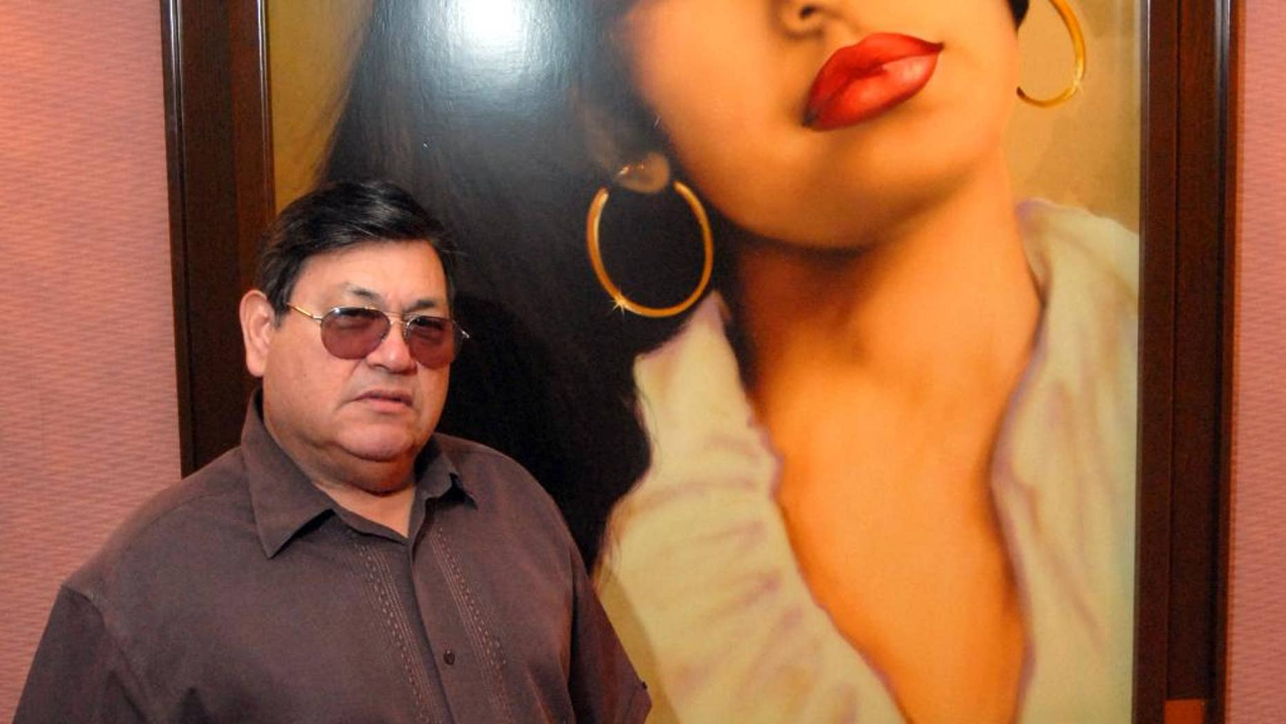 In this June 24, 2011, file photo, Abraham Quintanilla, the father of the late singer Selena, poses in front of an air brush work of art that a fan gave him after her death, hanging in the studio at Q Productions in Corpus Christi, Texas, where Selena made her last recording.