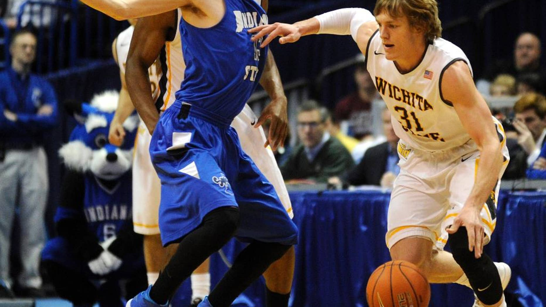 Wichita State's Ron Baker (31) drives by Indiana State's Jake Odum, left, in the first half of an NCAA college basketball game in the championship of the Missouri Valley Conference men's tournament on Sunday, March 9, 2014, in St. Louis. (AP Photo/Bill Boyce)