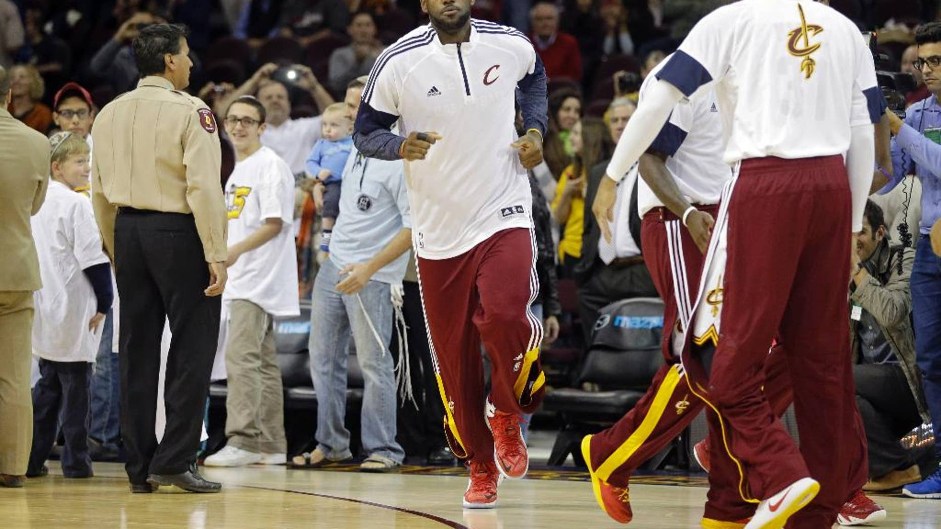 Cleveland Cavaliers' LeBron James takes the floor for warmups before a preseason basketball game against Maccabi Tel Aviv Sunday, Oct. 5, 2014, in Cleveland. (AP Photo/Mark Duncan)