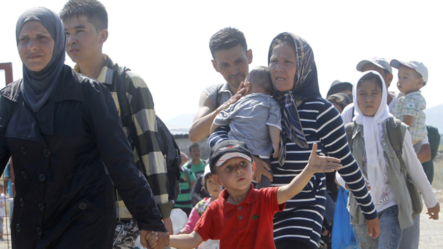 Aug. 31, 2015: A group of migrants with children arrive at the transit center for migrants, after crossing the border from Greece to Macedonia.