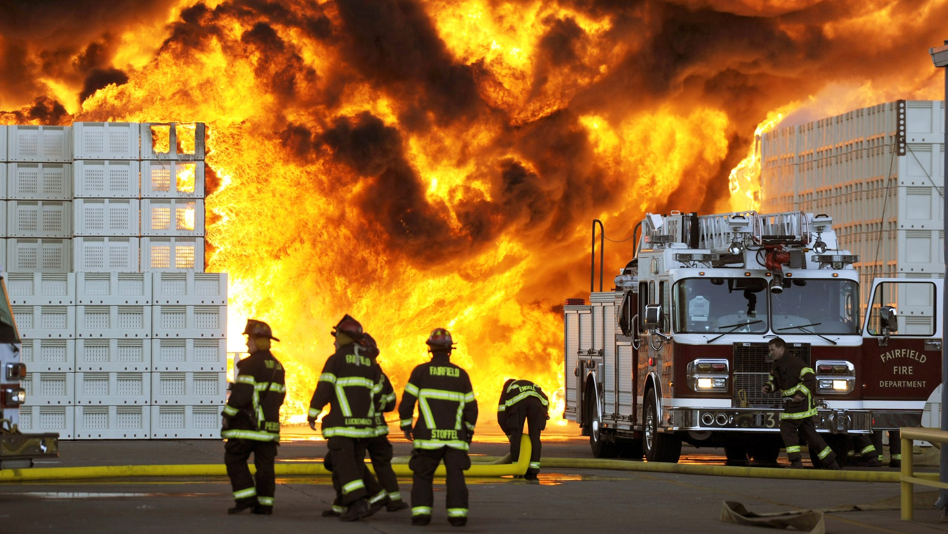 July 26: Firefighters prepare to reposition their ladder truck during their attack of a 6-alarm fire at the Macro Plastics manufacturing facility in Fairfield, California.  According to fire officials, the 1:15 p.m. blaze started in the storage yard housing hundreds of plastic containers used for shipping agricultural products.