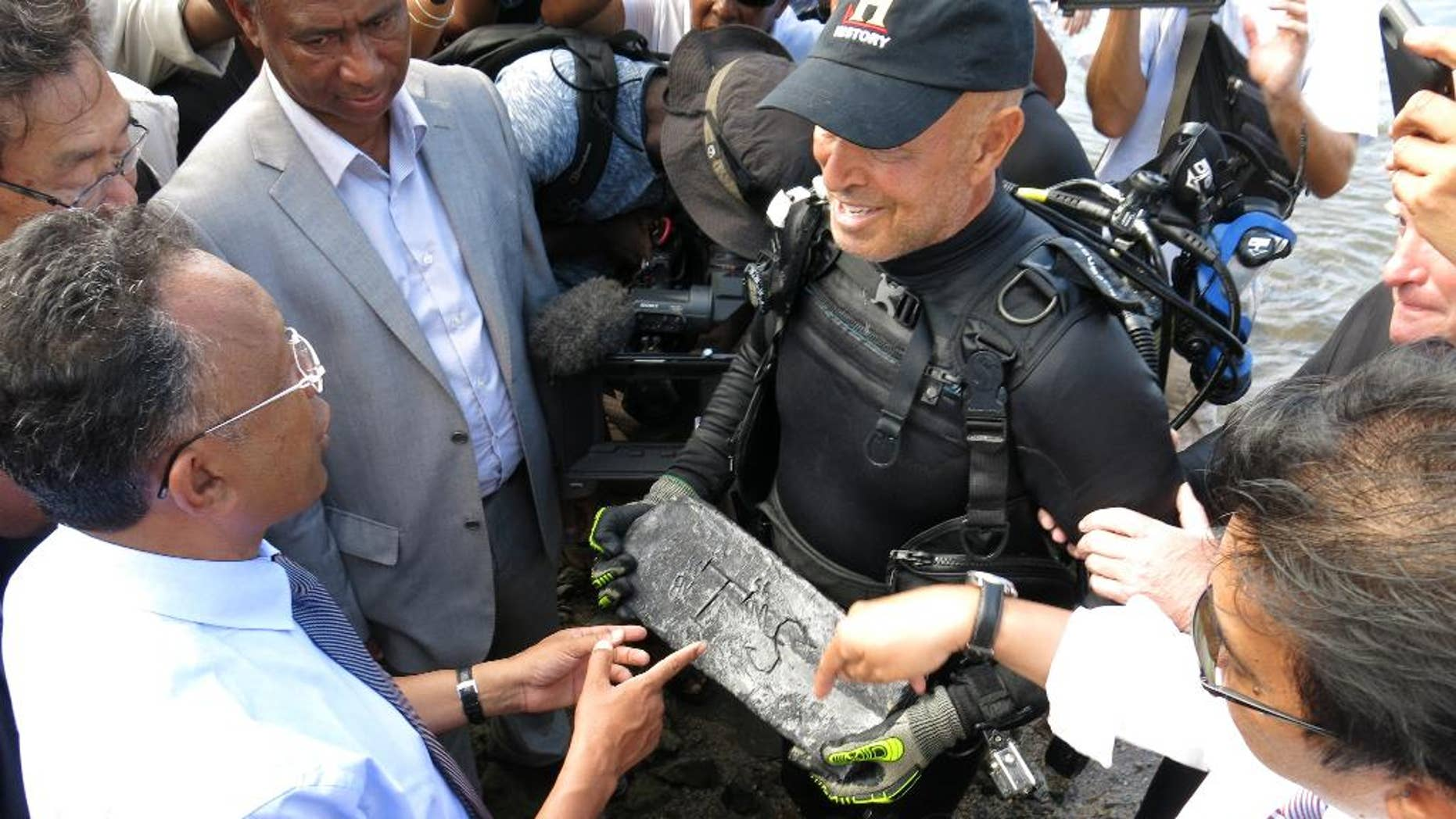 In this photo taken Thursday, May, 7, 2015 underwater explorer Barry Clifford, right, presents a silver bar he believes is part of the treasure of the pirate Captain Kidd, to the president of Madagascar, Hery Rajaonarimampianina, left, on Sainte Marie Island, Madagascar. (AP Photo/Martin Vogl)