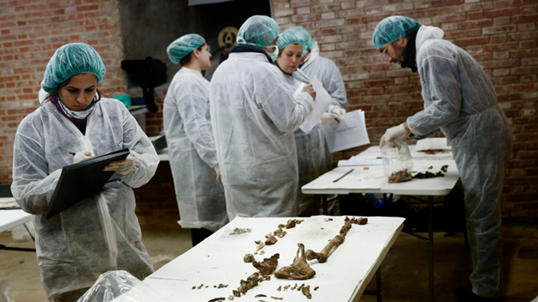 A team of archaeologists and anthropologists take notes after starting the excavation work after identifying three unrecorded and unidentified graves in the chapels crypt of the closed order Convent of the Barefoot Trinitarians in Madrid's historic Barrio de las Letras, or Literary Quarter, Spain, Saturday, Jan. 24, 2015. Experts searching for the remains of Miguel de Cervantes hope they may be entering the final phase of their nine-month quest to solve the mystery of where the great Spanish writer was laid to rest. The 'Don Quixote' author was buried in 1616 at the Convent but the exact whereabouts of his grave in the tiny convent chapel are unknown. The bones found will be exhumed and analyze, after that, the experts will try to identify the bones using DNA profiling. (AP Photo/Daniel Ochoa de Olza)