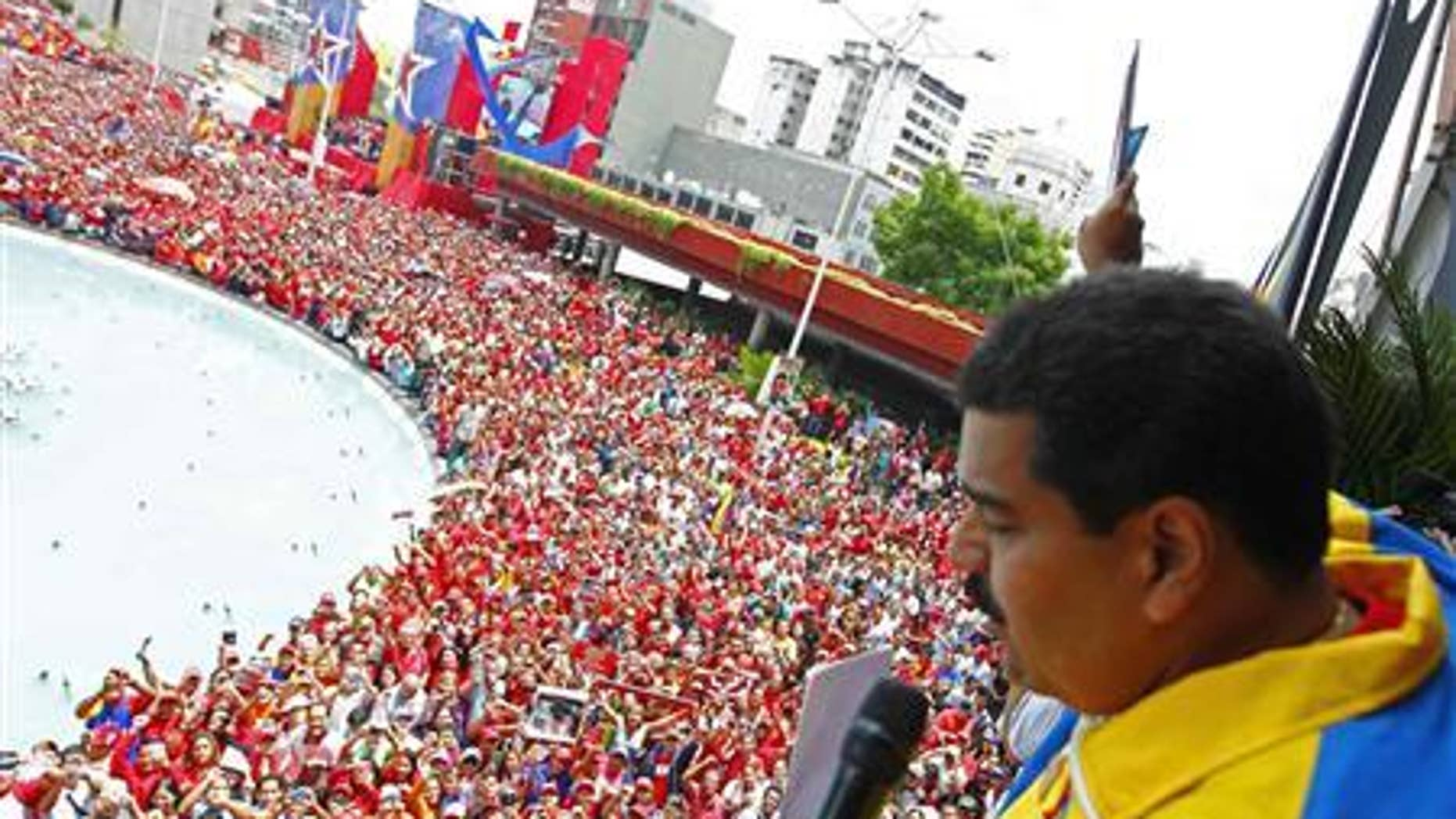 Venezuela's acting President, Nicolas Maduro, gestures to supporters after he registered as a candidate for president in the April 14th election outside the national election board in Caracas March 11, 2013. REUTERS/Carlos Garcia Rawlins