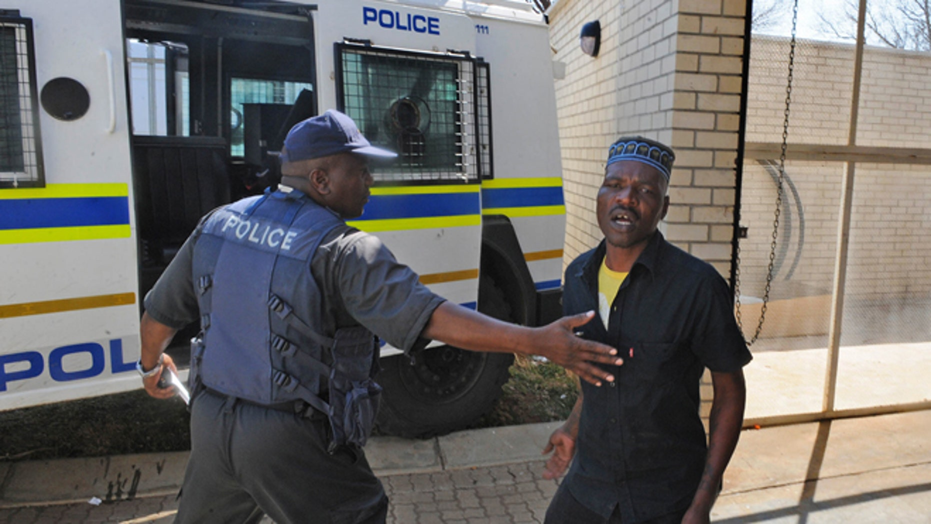 August 22, 2012: Chris Mahlangu, right, is led away from the court in Ventersdorp, South Africa after receiving a life sentence for the murder of right wing leader Eugene TerreBlanche.