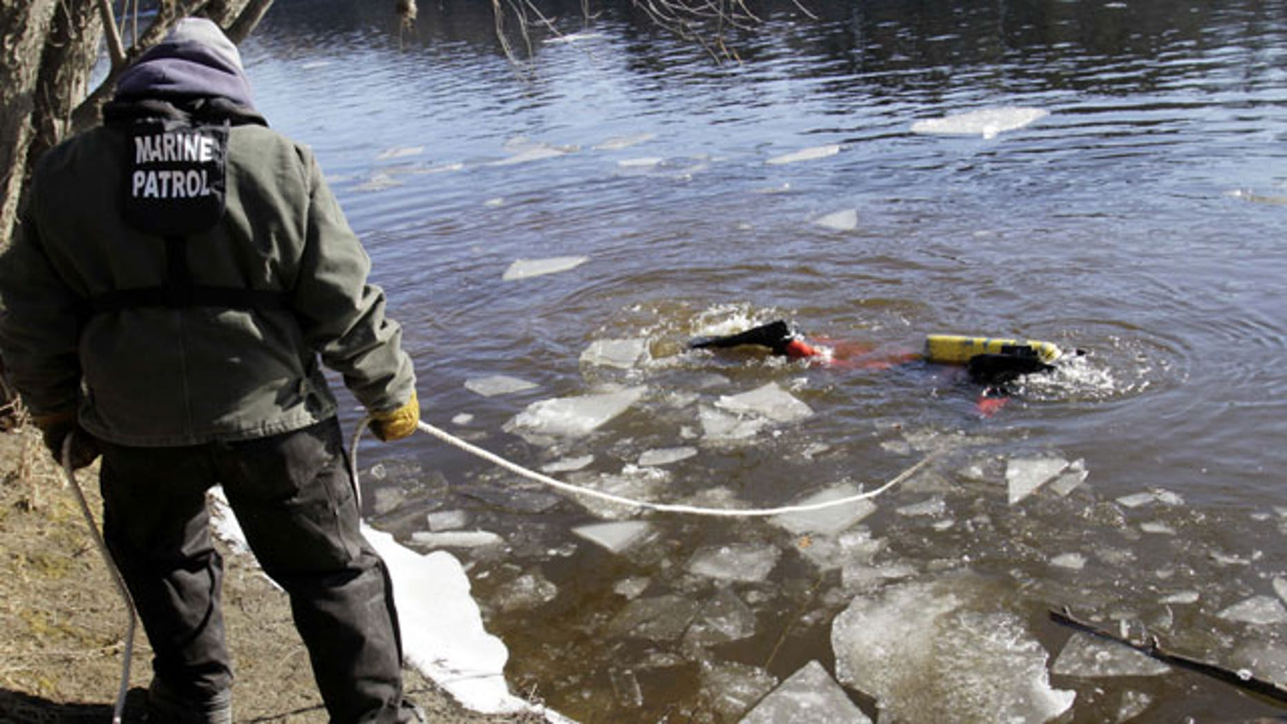January 11, 2012: A diver maneuvers around sheets of ice as he searches the Kennebec River in Waterville, Maine for 20-month-old Ayla Reynolds who was reported missing since December.