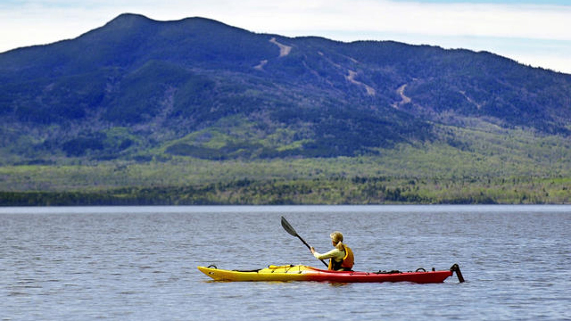 Kayaker paddles on Moosehead Lake at Lily Bay State Park, Beaver Cove, Maine.