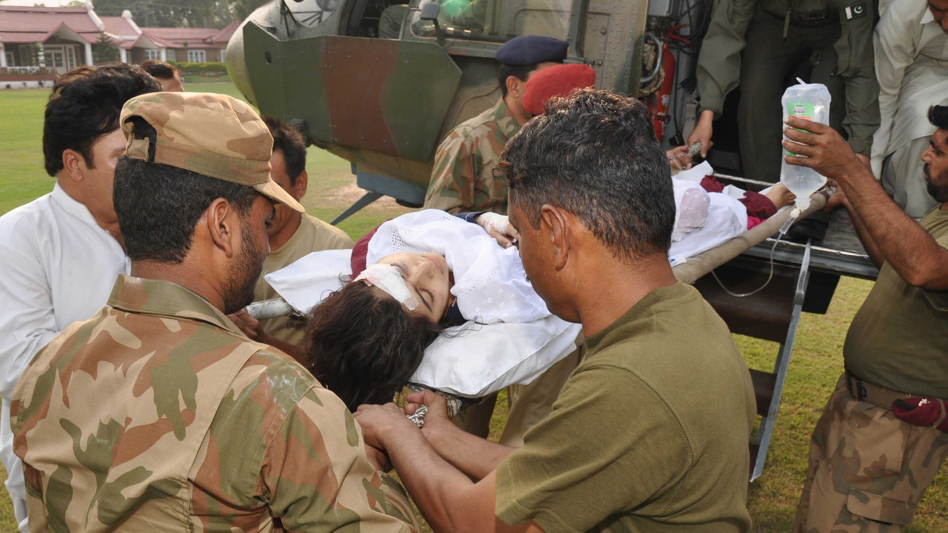 In this photo released by Inter Services Public Relations department, Pakistani soldiers carry wounded Pakistani girl, Malala Yousufzai, from a military helicopter to a military hospital in Peshawar, Pakistan.