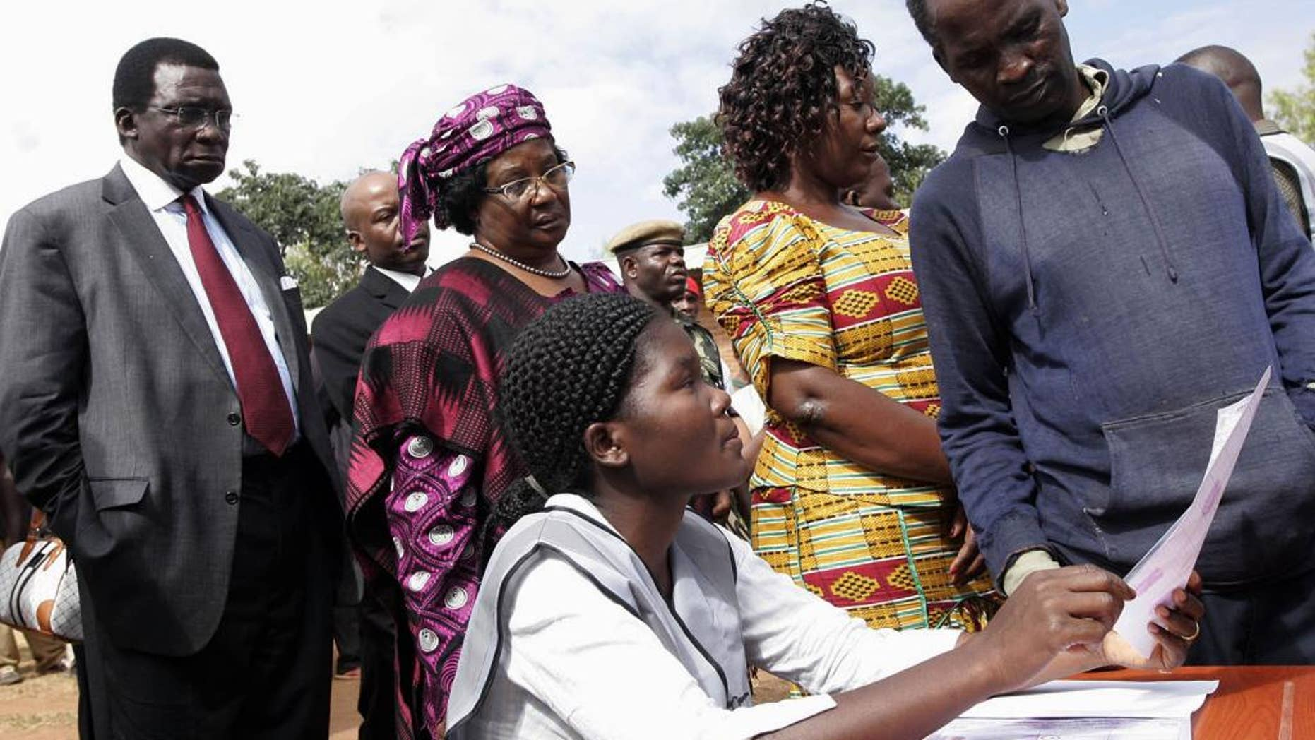 Background from left to right, Chief Justice Richard Banda, his wife, Malawi President Joyce Banda, and  younger sister  Anjimile Mtila-Oponyo, join a voting queue  to cast their votes in the eastern district of Zomba, Malawi, Tuesday, May 20, 2014. Africa's second female president Joyce Banda is facing stiff challenges from a field of 12 candidates in Malawi's elections Tuesday. (AP Photo/Raphael Tenthani)