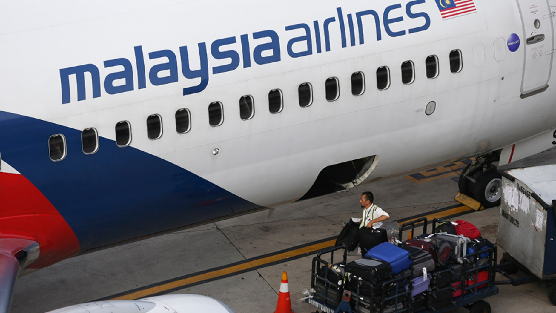 A Malaysia Airlines ground staff member unloads luggage from a plane at Kuala Lumpur International Airport in Sepang, Malaysia Monday, June 1, 2015.