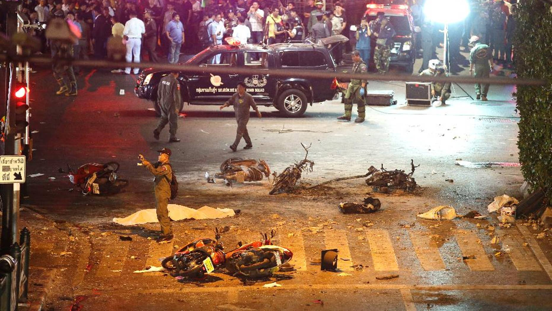FILE - In this Aug. 17, 2015 file photo, a policeman photographs debris from an explosion in central Bangkok, Thailand. A Pakistani and two Malaysians have been detained in connection with last month's bombing of a shrine in Bangkok that killed 20 people, the national police chief said Monday, Sept. 14, 2015. (AP Photo/Mark Baker, File)