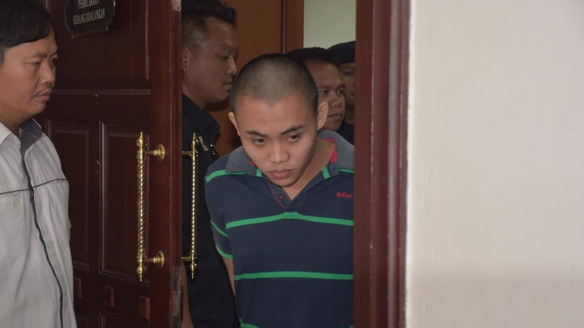 Zulkipli Abdullah, 23, center, walks out from a courtroom in Kuching, Malaysia, on Tuesday, March 31, 2015. On Tuesday, Prosecutor Muhamad Iskandar Ahmad said the high court found Zulkipli guilty of stabbing to death Aidan Brunger and Neil Gareth Dalton, two British medical students, on Borneo island last August. (AP Photo)