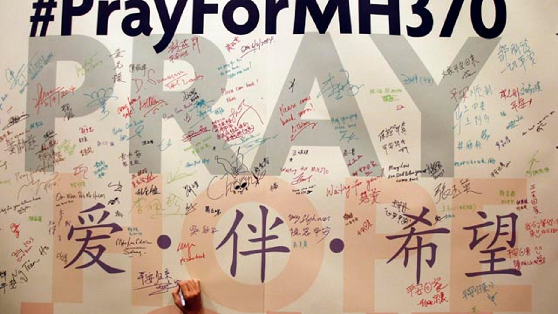 FILE - In this April 6, 2014 file photo, a man writes messages for passengers aboard the missing Malaysia Airlines Flight MH370 before a mass prayer for them, in Kuala Lumpur, Malaysia. (AP Photo/Lai Seng Sin, File)