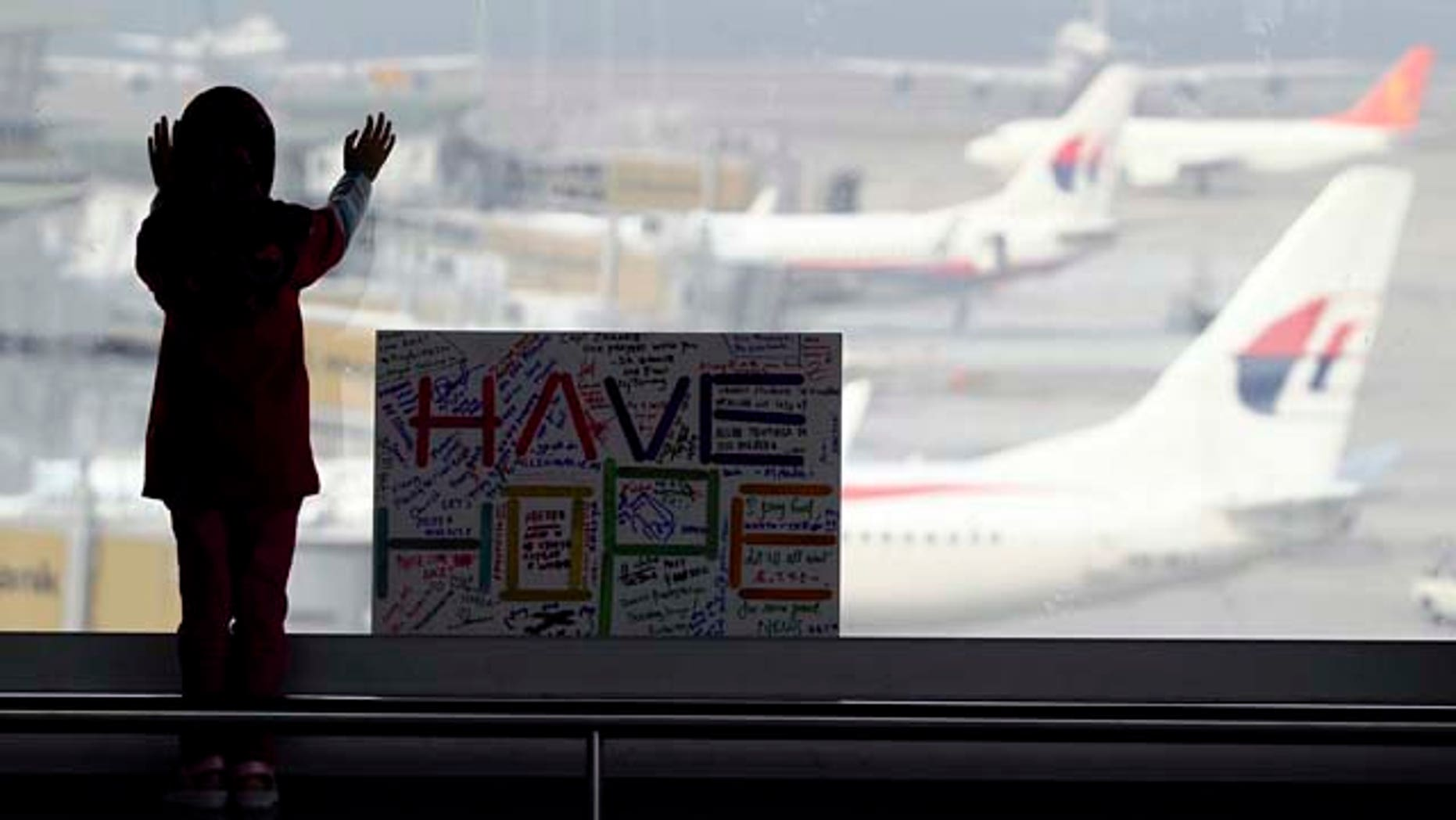 FILE - In this March 10, 2014 file photo, a woman looks at Malaysian planes next to a sign made and written by the public, wishing for the safe return of passengers aboard the missing Malaysia Airlines Flight 370 plane at Kuala Lumpur International Airport in Sepang, Malaysia. (AP Photo/Daniel Chan, File)