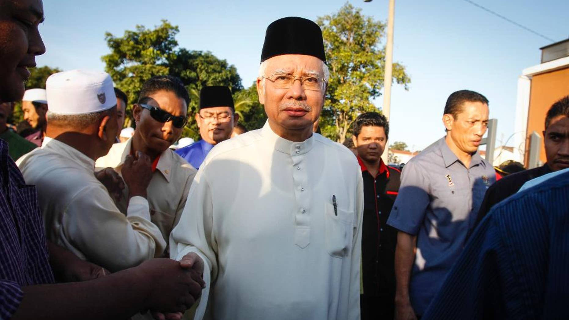 Malaysian Prime Minister Najib Razak arrives for a Ramadan breakfast at a mosque in Semenyih outside Kuala Lumpur, Malaysia on Sunday, July 5, 2015. Razak is facing the risk of criminal charges over allegations that hundreds of millions of dollars were funneled from an indebted state fund to his personal bank accounts, the first time a Malaysian leader has faced criminal allegations. (AP Photo/Joshua Paul)