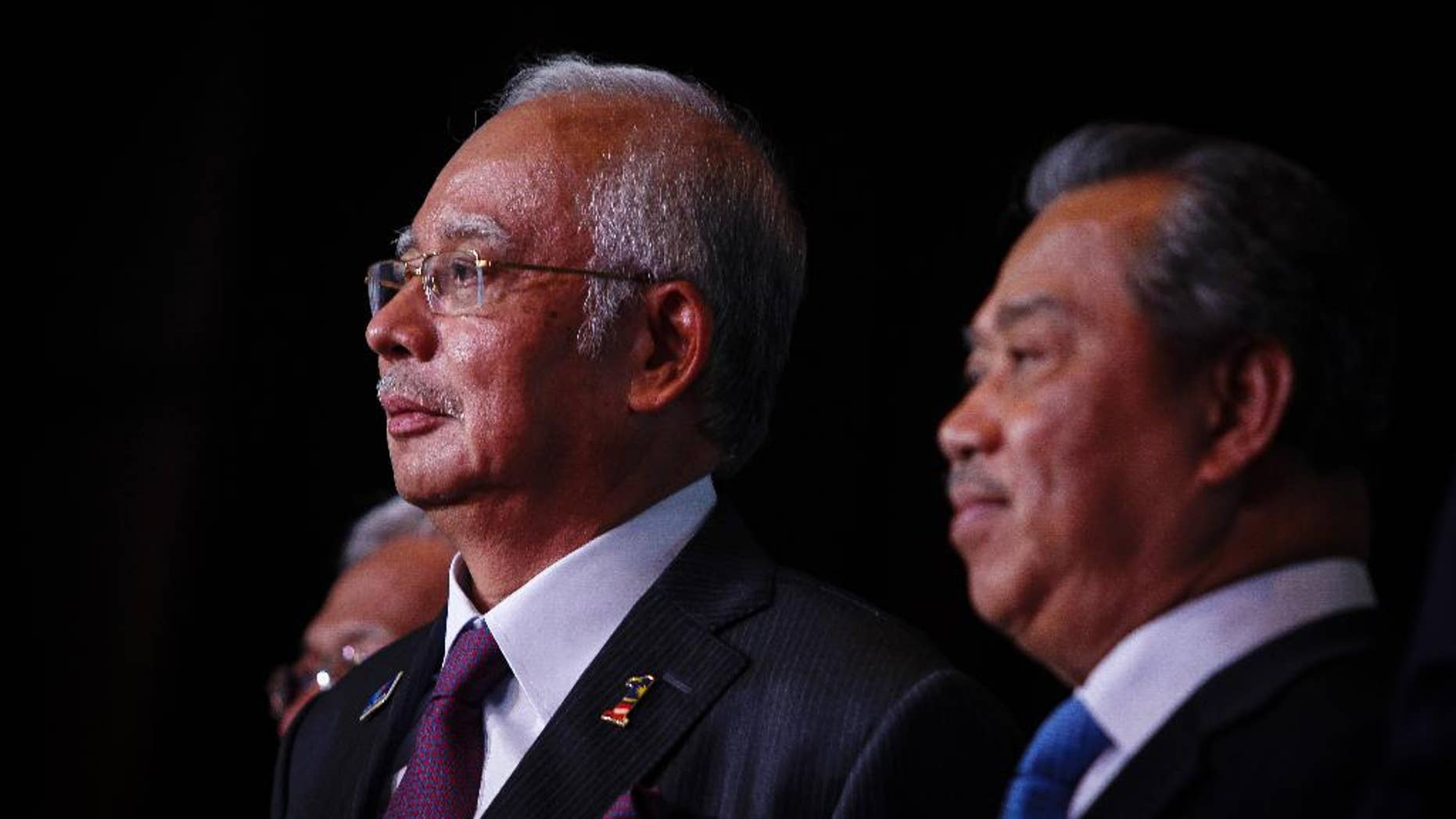 In this April 7, 2015 photo, Malaysian Prime Minister Najib Razak, left, and Deputy Prime Minister Muhyiddin Yassin attends the launch of the Malaysian Education Blue Print at a hotel in Kuala Lumpur, Malaysia. In an interview Thursday April 9, 2015, Najib pledged there will be no cover-up in the investigation of a debt-laden state investment fund and reiterated he is not involved in the murder of a Mongolian woman nine years ago. (AP Photo/Joshua Paul)