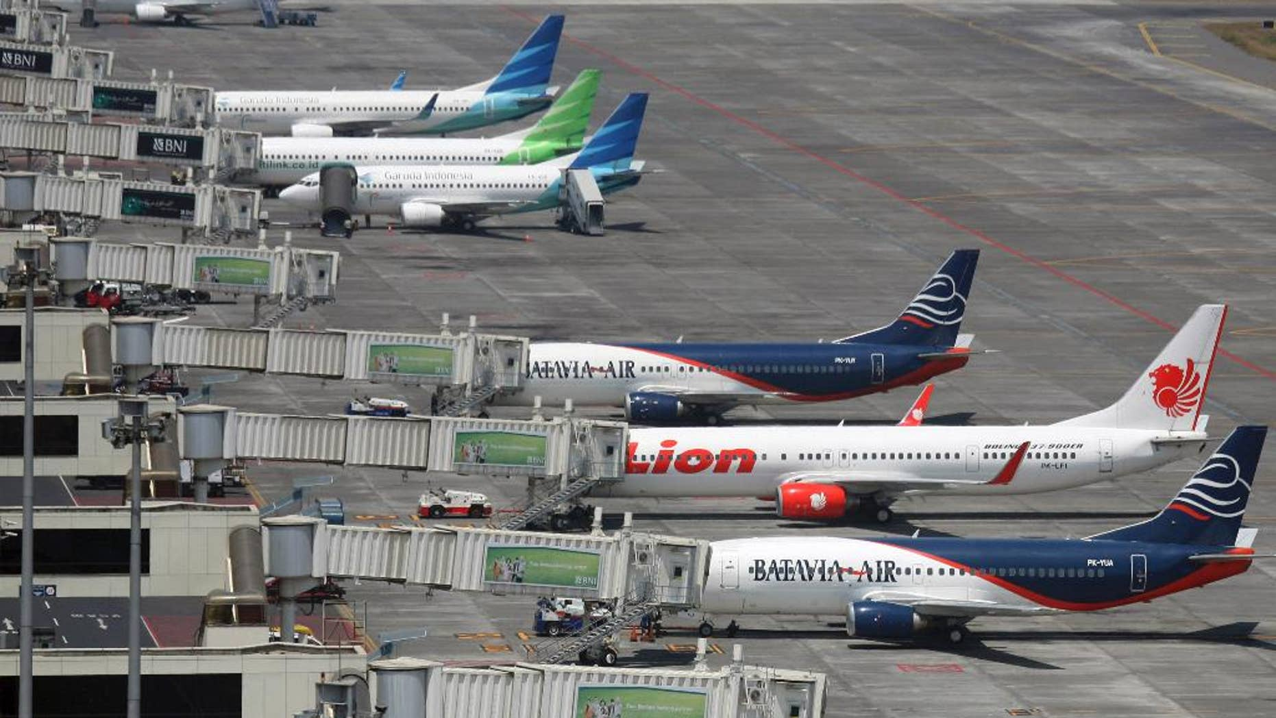 FILE - In this Sept. 25, 2012 file photo, budget airlines' passenger jets, Malaysia's AirAsia, top, Indonesia's Badavia Air, third from bottom, and Indonesia's Lion Air, second bottom, are parked on the tarmac with Indonesian planes of domestic airline Merpati Nusantara, second top, and the flagship carrier Garuda Indonesia at Juanda International Airport in Surabaya, East Java, Indonesia. Air travel in Asia is surging as the middle class gets bigger, discount airlines proliferate and business ties with the rest of the world deepen. (AP Photo/Trisnadi, File)