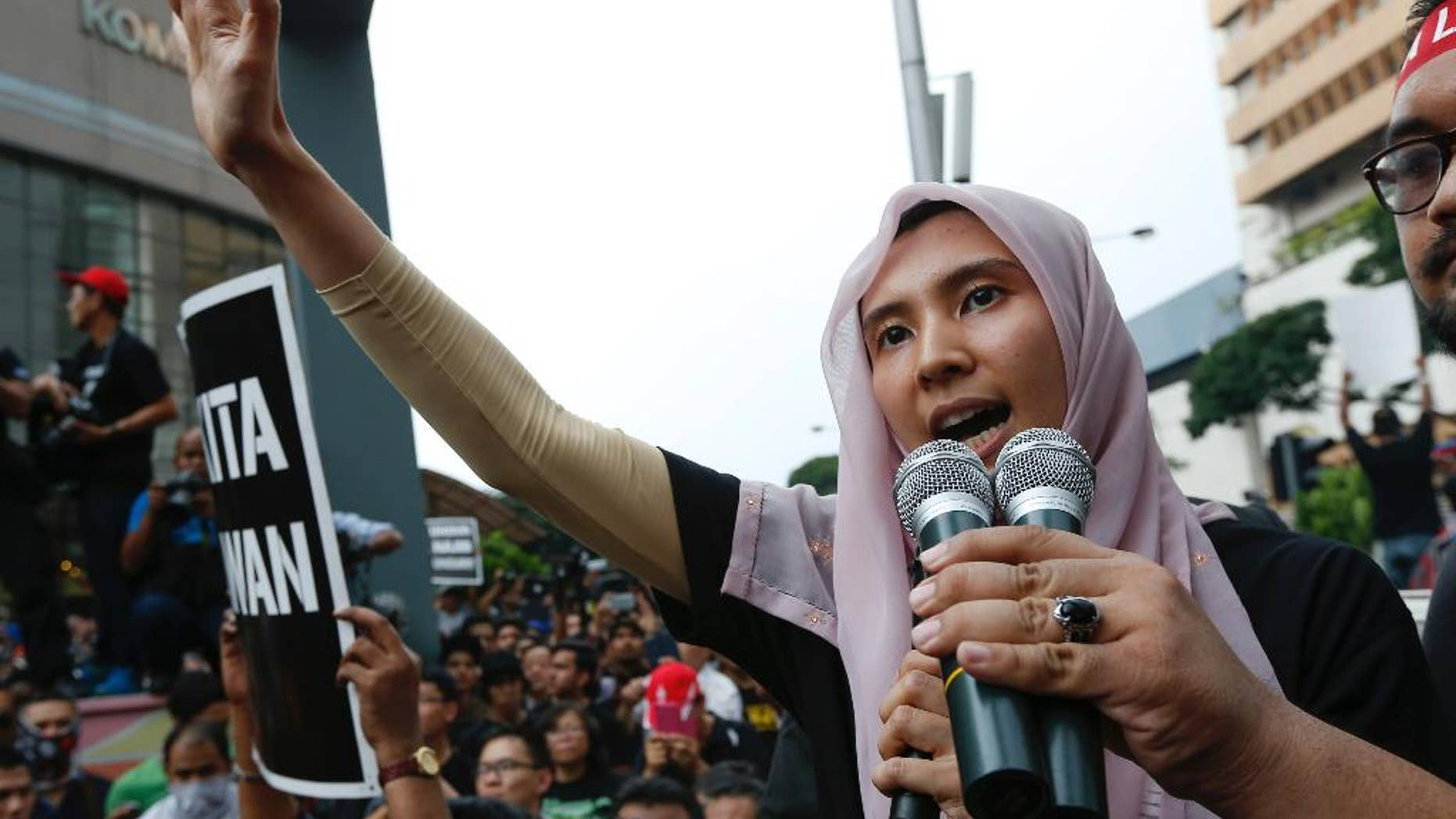 FILE - In this  Saturday, March 7, 2015 file photo, lawmaker and a vice-president of the People's Justice Party Nurul Izzah Anwar, daughter of oppression leader Anwar Ibrahim, speaks to protesters as they gather to demand the freedom of Anwar, in downtown Kuala Lumpur. Malaysian police arrested Monday, March 16, the eldest daughter of jailed Anwar Ibrahim for alleged sedition, a move slammed by critics as a clampdown on dissent. He began a 5-year prison sentence on Feb. 10 after being found guilty of sodomizing a former male aide in 2008. Anwar has maintained his innocence and claims he is a victim of a political vendetta by the government. (AP Photo/Vincent Thian, File)