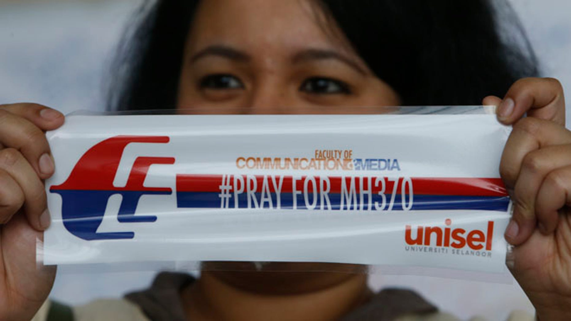 March 16, 2014.: A woman with a sticker on  the passengers of the missing Malaysia flight, at Kuala Lumpur International Airport, Malaysia.