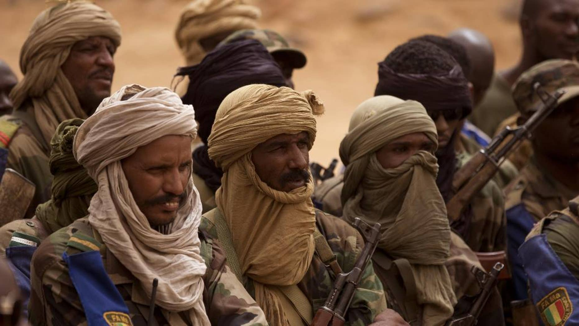 FILE - In this July 27, 2013 file photo, Malian Tuareg soldiers loyal to Col. Major El-Hadj Gamou listen during a visit by Mali's army chief of staff in Kidal, Mali. Tuareg separatist rebels agreed to sign a peace deal with the government in just over a week's time but that hasn't stopped them from attacking towns and encroaching further south toward Mali's capital. The toll has risen to 30 dead in recent days. (AP Photo/Rebecca Blackwell, File)