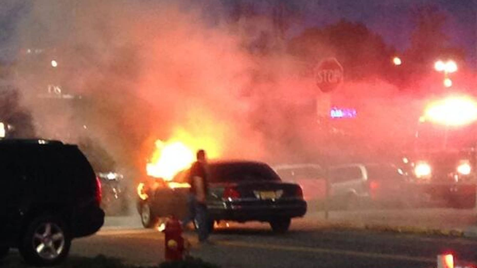 This photo provided by Brittany Berdy shows a car fire that authorities believe may have led to reports of gunshots that forced them to evacuate the Garden State Plaza mall in Paramus, N.J., Saturday, May 10, 2014. New Jersey State Police Capt. Stephen Jones said that police have found no evidence that any shots were fired at the mall Saturday night. (AP Photo/Brittany Berdy)