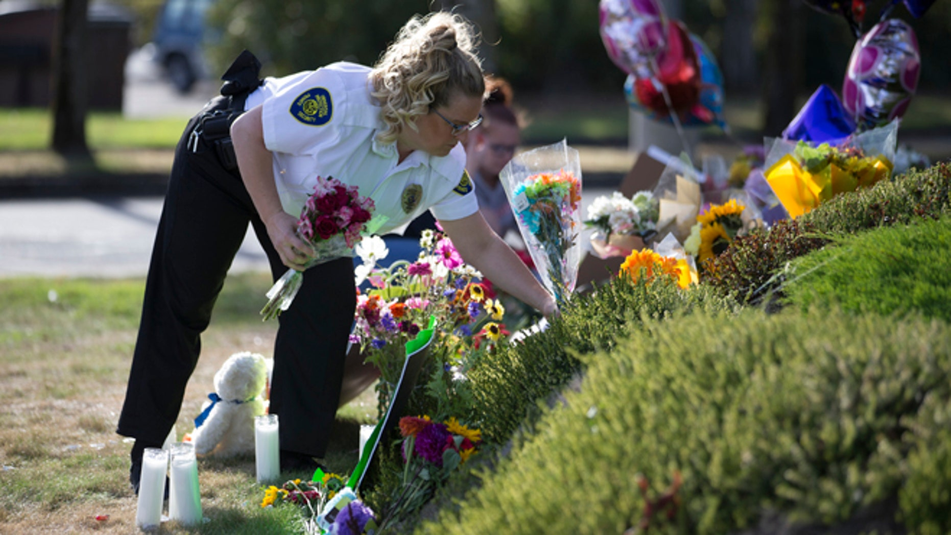 A security guard working at the Cascade Mall places flowers at a makeshift memorial on Sunday, Sept. 25, 2016, in Burlington, Wash., to the five victims killed in a shooting at the mall on Friday. The 20-year-old man suspected of killing the five people with a rifle at a Macy's makeup counter had a string of run-ins with the law in recent years, including charges he assaulted his stepfather. (AP Photo/Stephen Brashear)