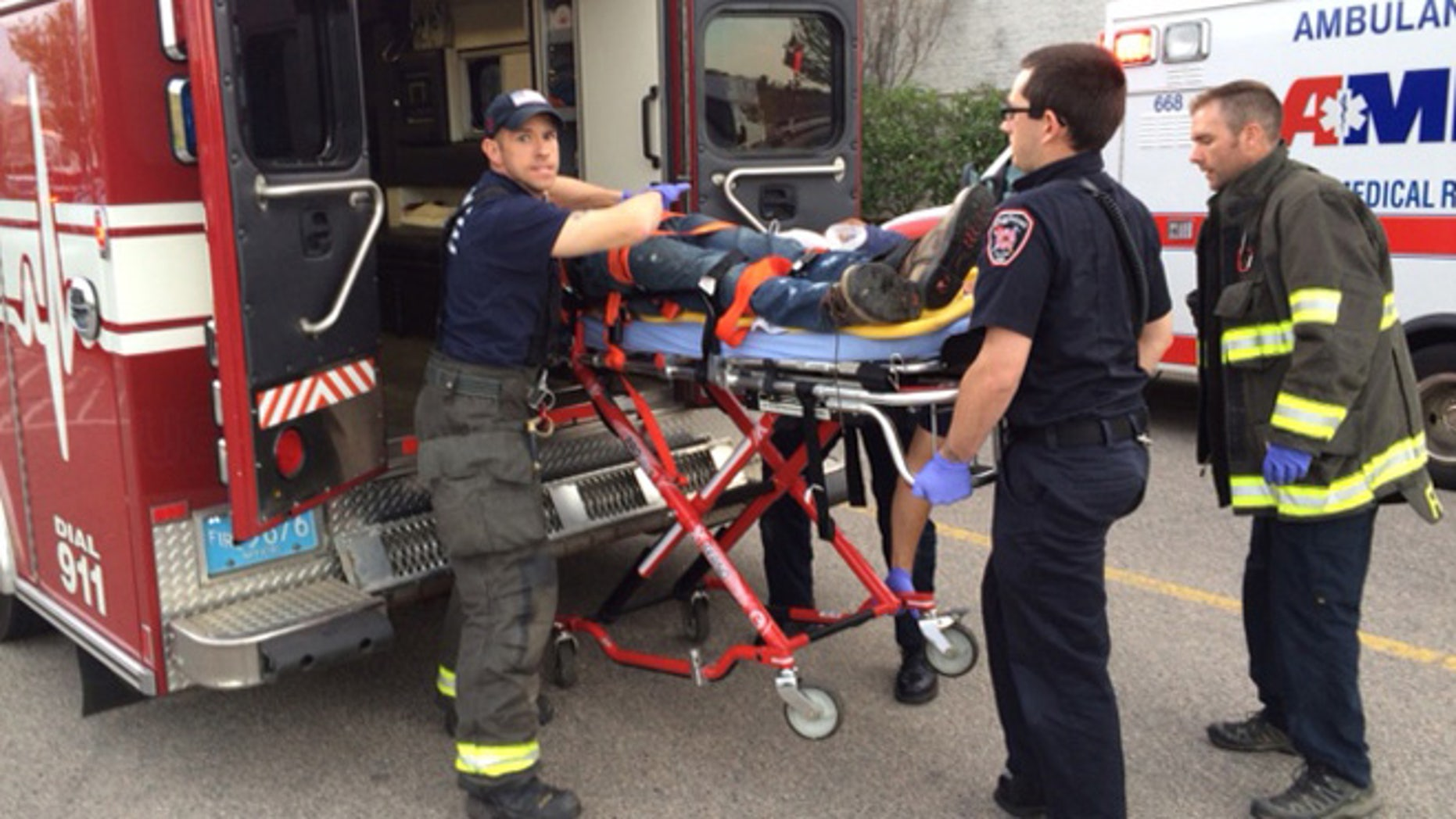 The suspect is transported on a gurney into an ambulance in Taunton, Mass., Tuesday, May 10, 2016.
