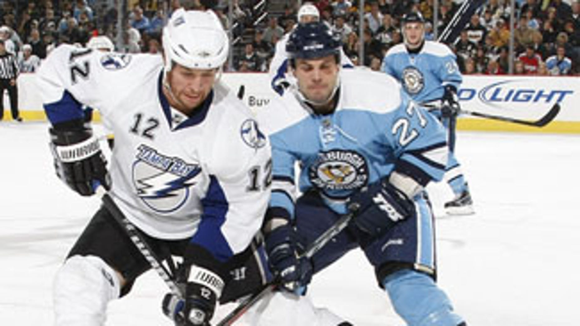 PITTSBURGH - OCTOBER 17:  Ryan Malone #12 of the Tampa Bay Lightning controls the puck in front of the defense of Craig Adams #27 of the Pittsburgh Penguins on October 17, 2009 at Mellon Arena in Pittsburgh, Pennsylvania.  (Photo by Gregory Shamus/NHLI via Getty Images) *** Local Caption *** Ryan Malone;Craig Adams