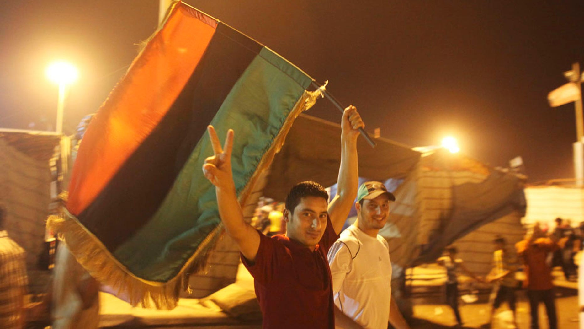 Aug. 22: A man flashes the victory sign as he celebrates the capture in Tripoli of Qaddafi's son and one-time heir apparent, Seif al-Islam, at the rebel-held town of Benghazi, Libya. It turned out that Seif al-Islam was not in custody and appeared Monday night in Tripoli.
