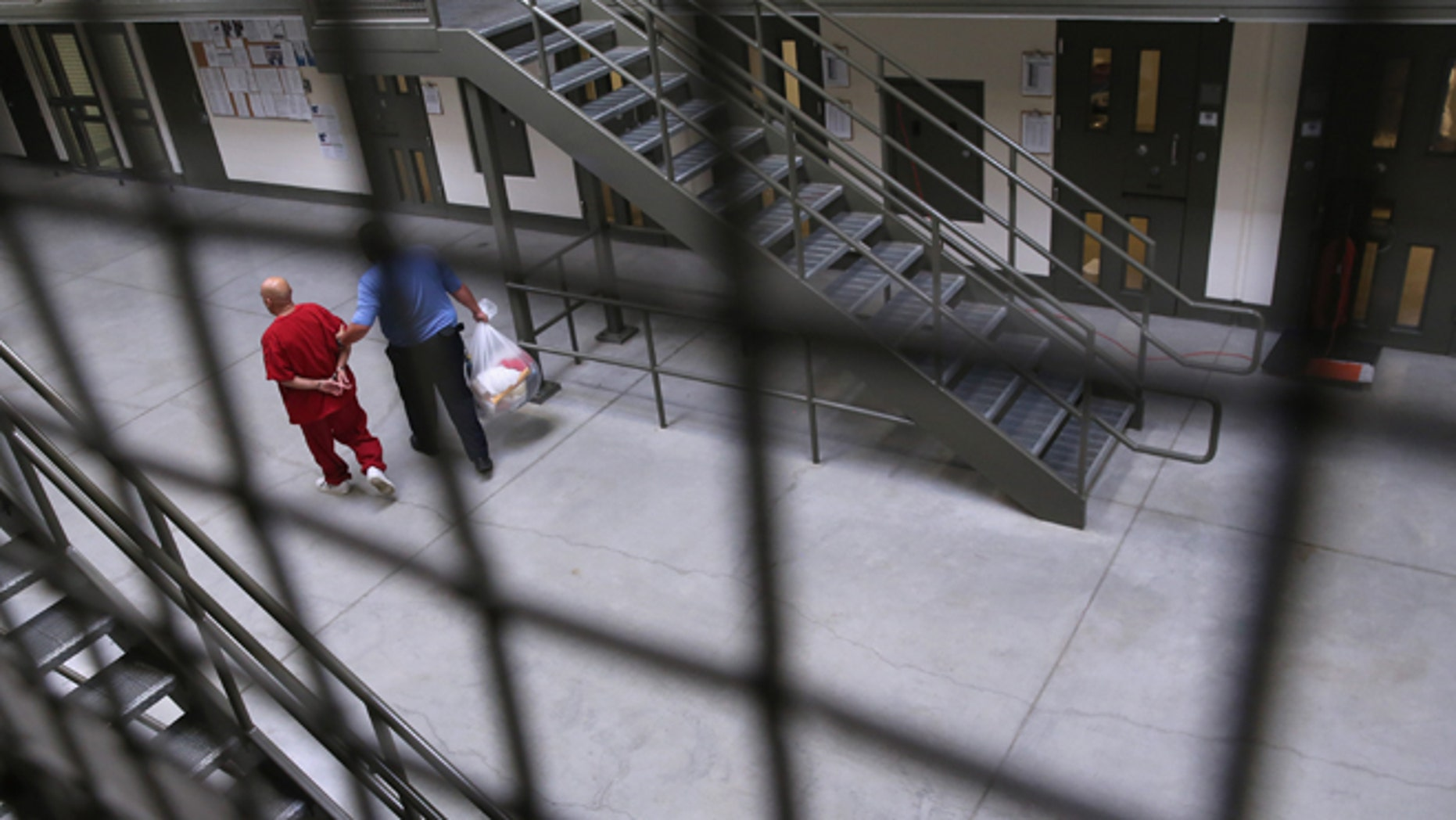 ADELANTO, CA - NOVEMBER 15: A guard escorts an immigrant detainee from his 'segregation cell' back into the general population at the Adelanto Detention Facility on November 15, 2013 in Adelanto, California. Most detainees in segregation cells are sent there for fighting with other immigrants, according to guards. The facility, the largest and newest Immigration and Customs Enforcement (ICE), detention center in California, houses an average of 1,100 immigrants in custody pending a decision in their immigration cases or awaiting deportation. The average stay for a detainee is 29 days. The facility is managed by the private GEO Group. ICE detains an average of 33,000 undocumented immigrants in more than 400 facilities nationwide. (Photo by John Moore/Getty Images)
