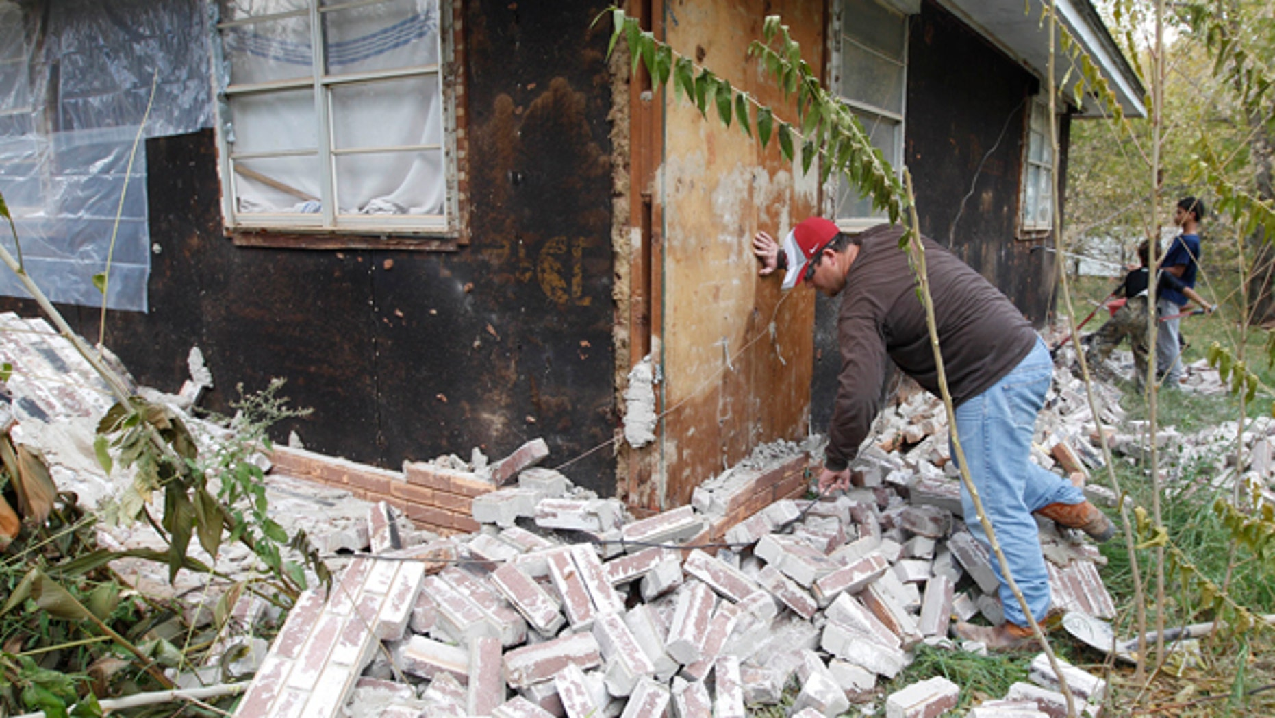 Nov. 6, 2011: Chad Devereaux examines bricks that fell from three sides of his in-laws home from an earthquake in Sparks, Okla.
