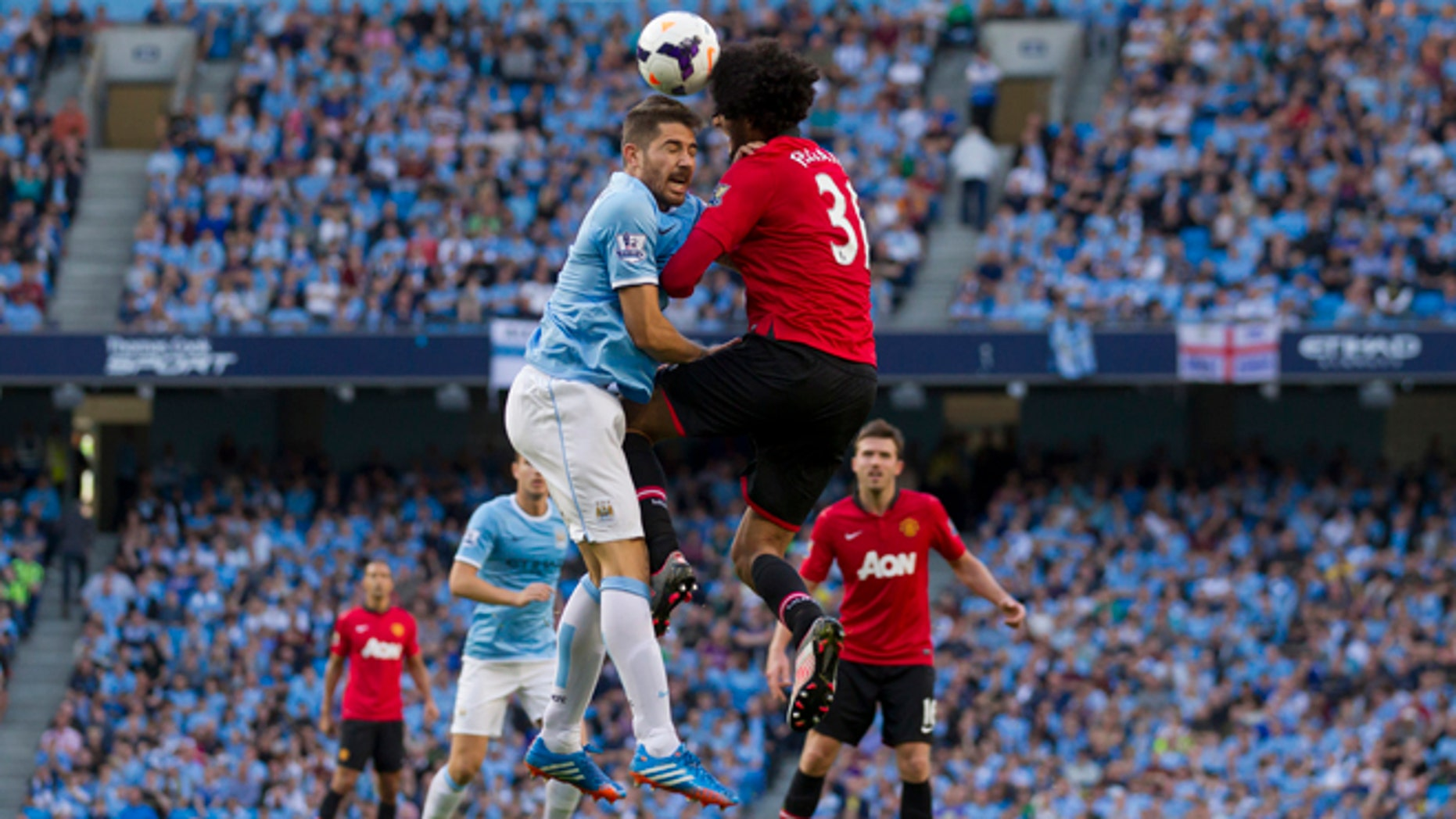 Manchester City's Aleksander Kolarov,  centre left, jumps for the ball against Manchester United's Marouane Fellaini during their English Premier League soccer match at the Etihad Stadium, Manchester, England, Sunday Sept. 22, 2013. (AP Photo/Jon Super)