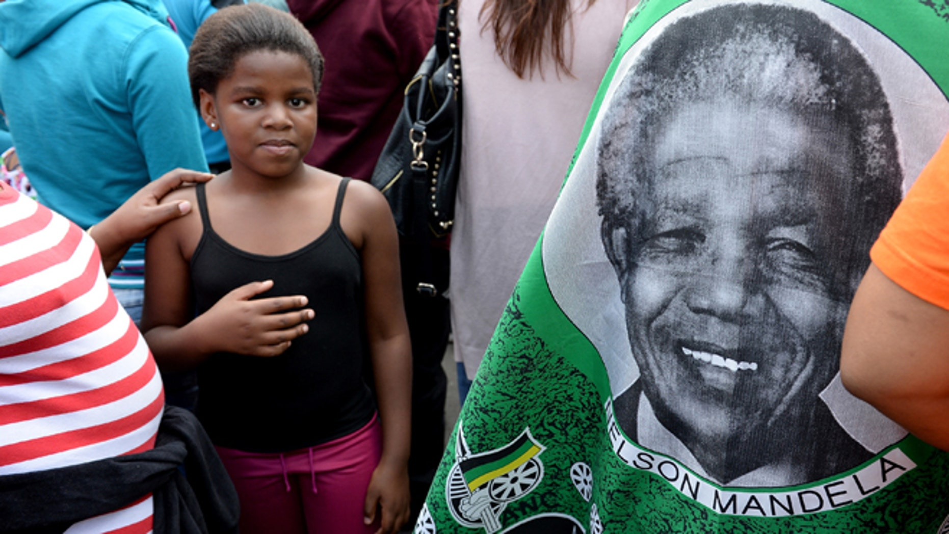 JOHANNESBURG, SOUTH AFRICA - DECEMBER 07:  South Africans gather to pay respect and tribute to former President Nelson Mandela outside his Houghton home on December 7, 2013 in Johannesburg, South Africa. Crowds gather at his home as vigils continue across South Africa as thousands mourn the death of former leader Nelson Mandela. Mr Mandela, died on Thursday aged 95, spent 27 years in jail before becoming South Africa's first black president in 1994..  (Photo by Jeff J Mitchell/Getty Images)