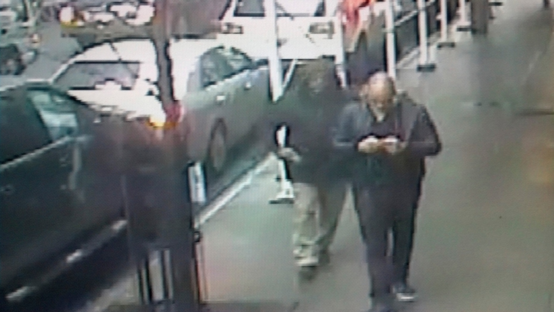 This still image made from a video provided by the New York City Police Department shows the gunman, left, behind Brandon Lincoln Woodard pulling the weapon from his jacket pocket a moment before the shooting.