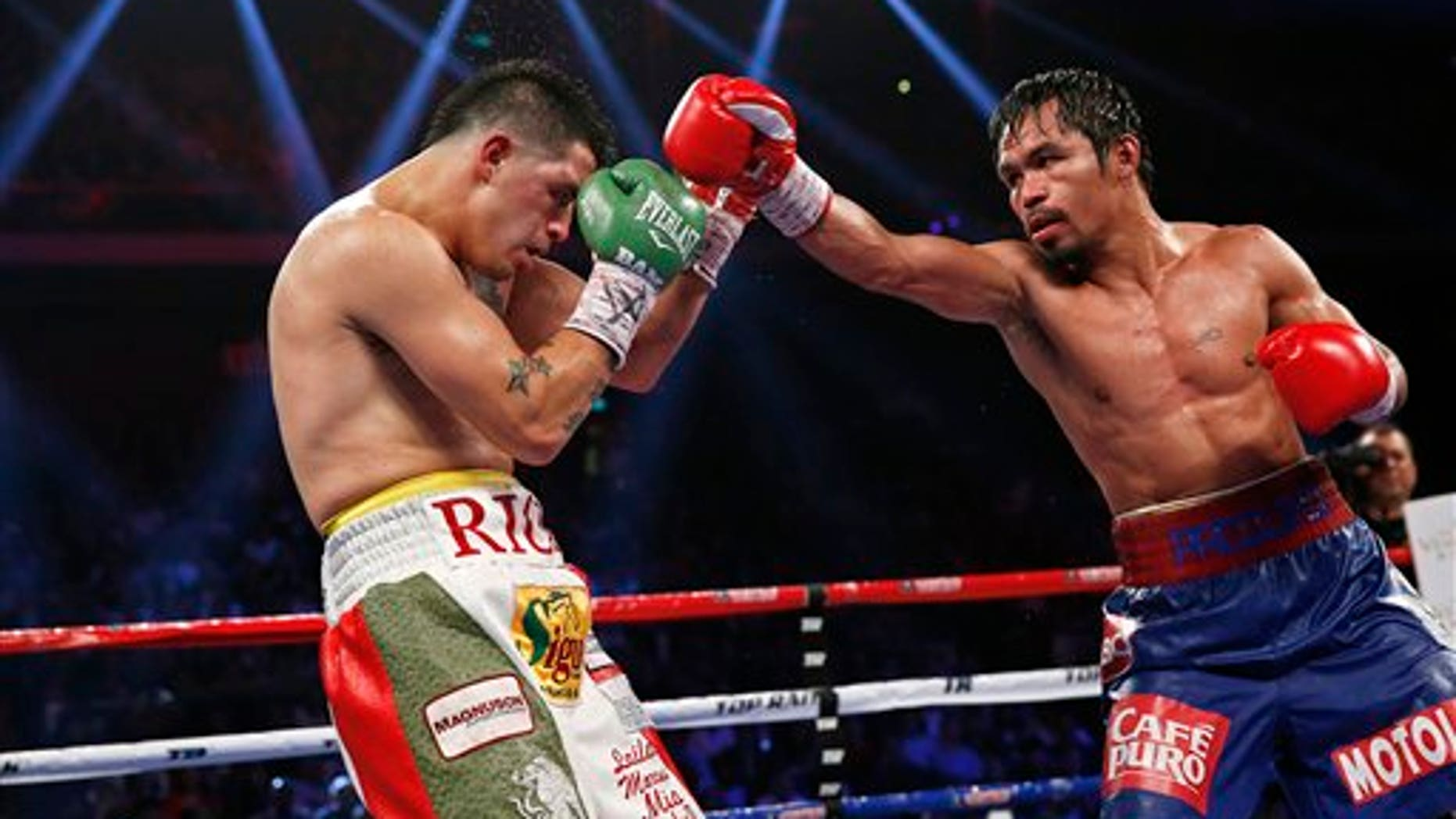 Manny Pacquiao, from the Philippines, right, punches Brandon Rios of the United States during their WBO international welterweight title fight Sunday, Nov. 24, 2013, in Macau. Pacquiao defeated Rios by unanimous decision on Sunday to take the WBO international welterweight title and return to his accustomed winning ways after successive defeats.   (AP Photo/ Vincent Yu)