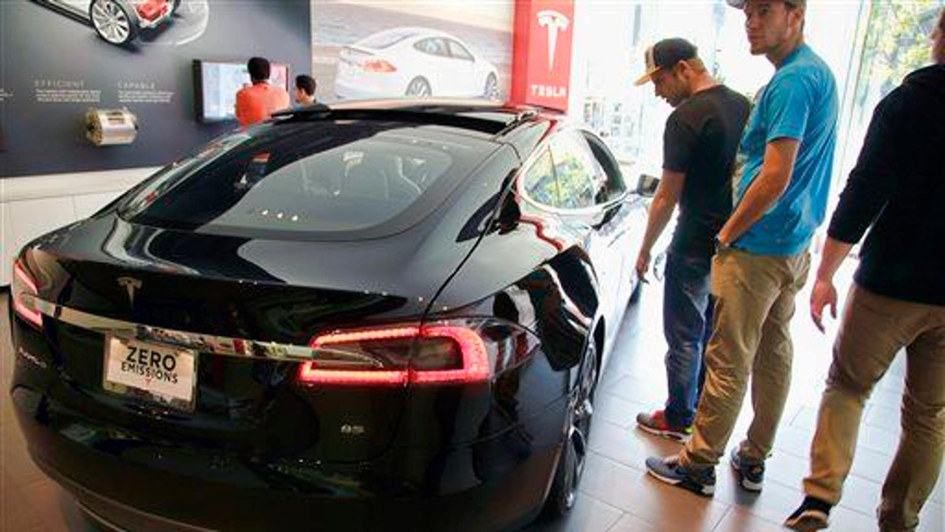 In this Saturday, Jan. 3, 2015 photo, people check out the Tesla model S at the Tesla showroom at the the Third Street Promenade in Santa Monica, Calif.