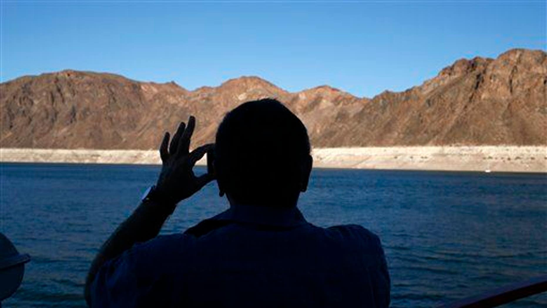 In this July 20, 2014 photo, a man takes a picture while taking a cruise at the Lake Mead National Recreation Area in Nevada.