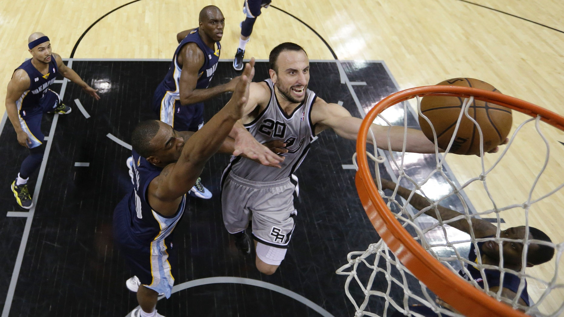 San Antonio Spurs' Manu Ginobili (20), of Argentina, drives to the basket as Memphis Grizzlies' Darrell Arthur, left, defends him during the second half in Game 1 of a Western Conference Finals NBA basketball playoff series, Sunday, May 19, 2013, in San Antonio. San Antonio won 105-83.(AP Photo/Eric Gay)