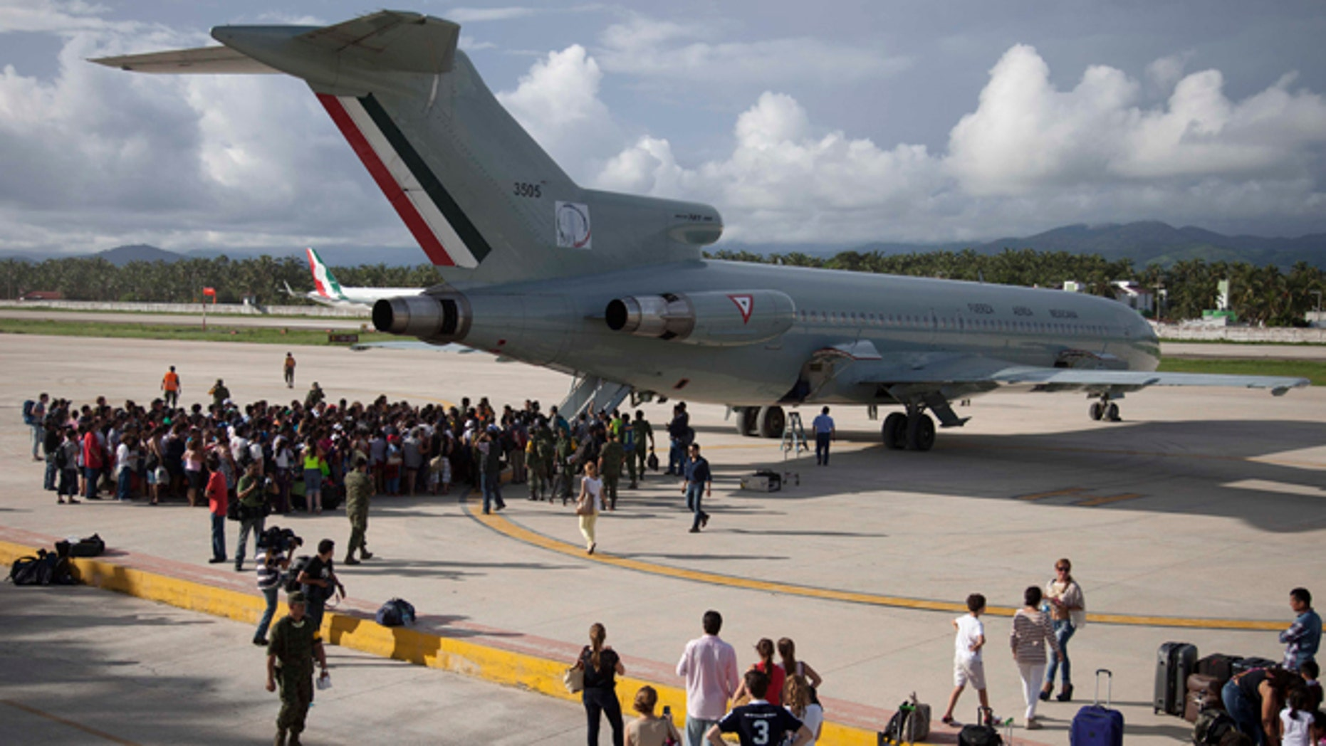 Hundreds of stranded tourists gather around a Mexican Air Force jet as they wait to be evacuated, at the air base in Pie de la Cuesta, near Acapulco, Mexico, Tuesday, Sept. 17, 2013. With roads blocked by landslides, rockslides, floods and collapsed bridges, Acapulco was cut off from road transport after Tropical Storm Manuel made landfall on Sunday. The airport as well, was flooded. Emergency flights began arriving in Acapulco to evacuate at least 40,000 mainly Mexican tourists stranded in the resort city. (AP Photo/Eduardo Verdugo)
