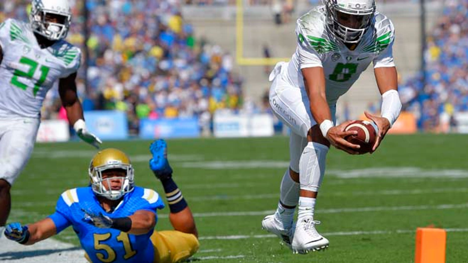 In this Oct. 11, 2014, file photo, Oregon quarterback Marcus Mariota, right, dives in for a touchdown as UCLA linebacker Aaron Wallace, center, misses the tackle and running back Royce Freeman looks on during the first half of an NCAA college football game in Pasadena, Calif.
