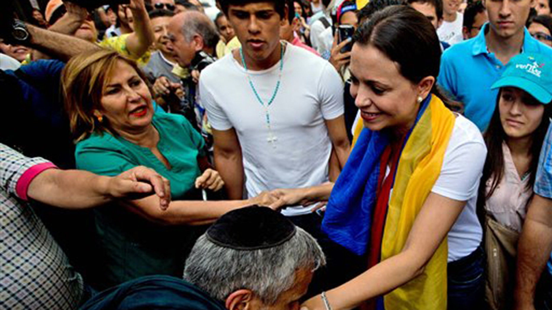 A man kisses the hand of leading opposition politician Maria Corina Machado as she arrives for a rally in Caracas, Venezuela, Wednesday, March 26, 2014. The head of Venezuela's congress, Diosdado Cabello, said Monday that Machado, who was stripped of her parliament seat, violated the constitution by addressing the Organization of American States last week at the invitation of Panama, which ceded its seat at the Washington-based group group so she could provide regional diplomats with a firsthand account of the unrest. (AP Photo/Fernando Llano)