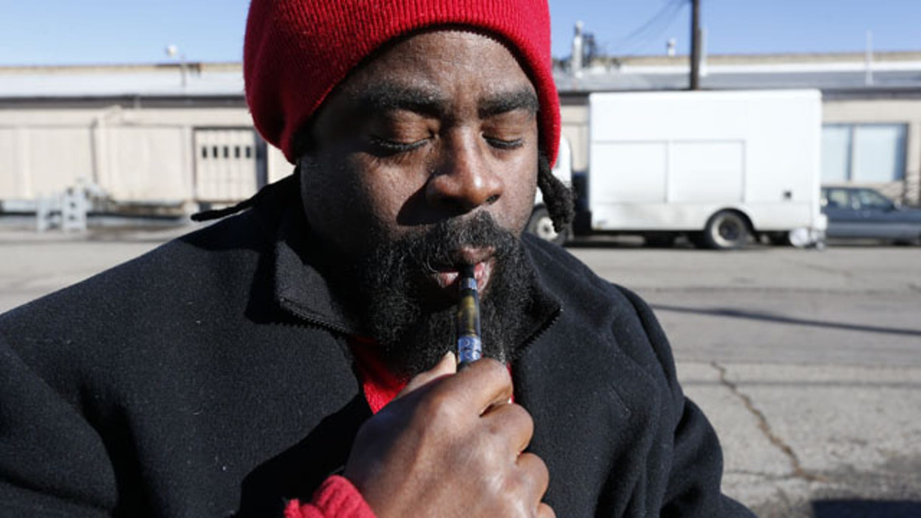 Nov. 26, 2014: Homeless man Chris Easterling smokes legal hash oil from a vaporizer pen to ease the pain of his multiple sclerosis in front of the Salvation Army shelter where he sleeps in Denver. Easterling was sick of relying on illegal drug dealers in Minneapolis when he needed marijuana to help ease the pain of MS. (AP Photo/Brennan Linsley)