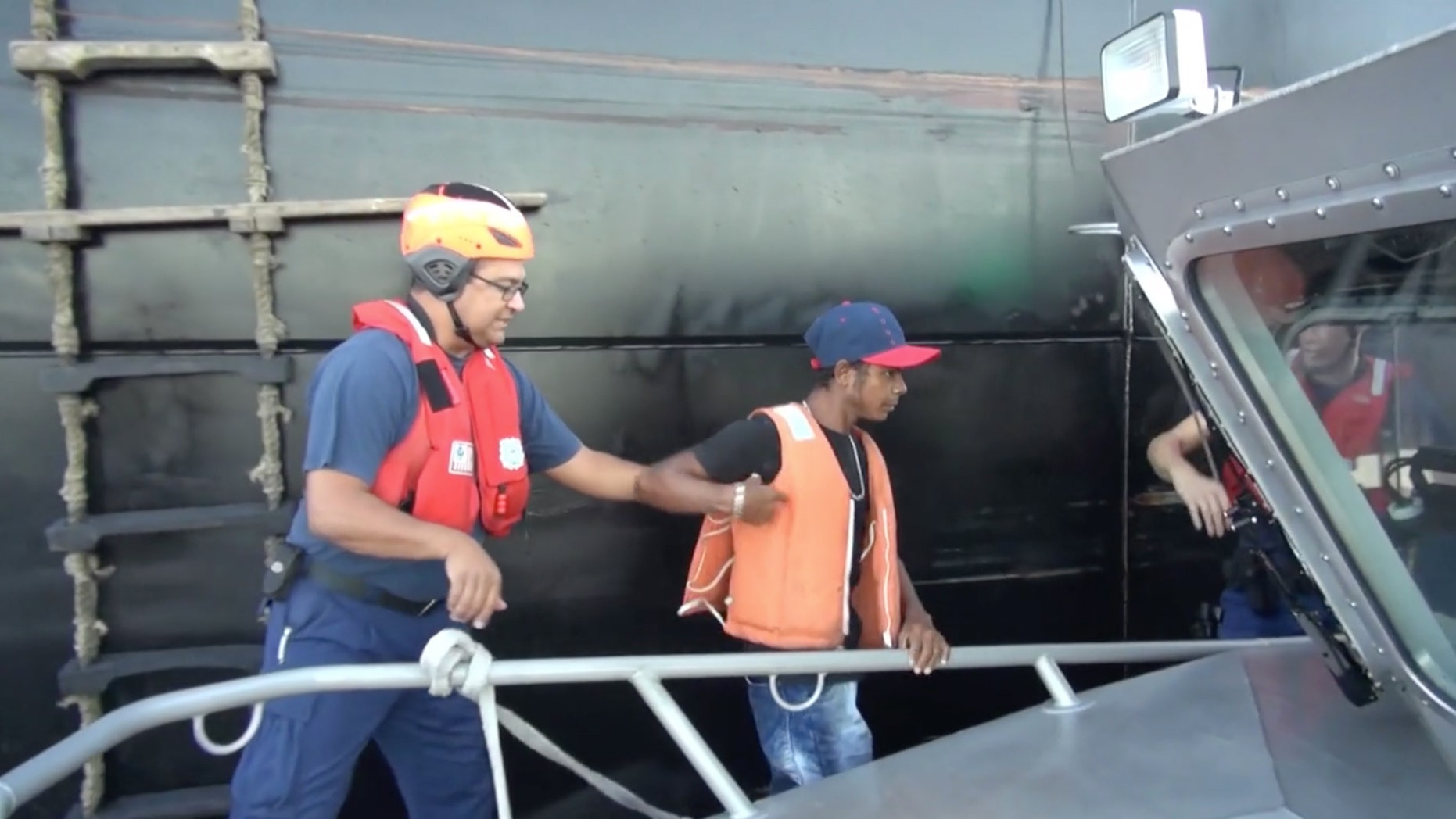In this Wednesday, May 4, 2016 image taken from video, an unidentified mariner, center, is helped onto a U.S. Coast Guard cutter after being rescued at sea more than 2,000 miles southeast of Hawaii. The Colombian man survived a two-month ordeal in the Pacific by eating fish and seagulls, the U.S. Coast Guard said. (U.S. Coast Guard via AP)