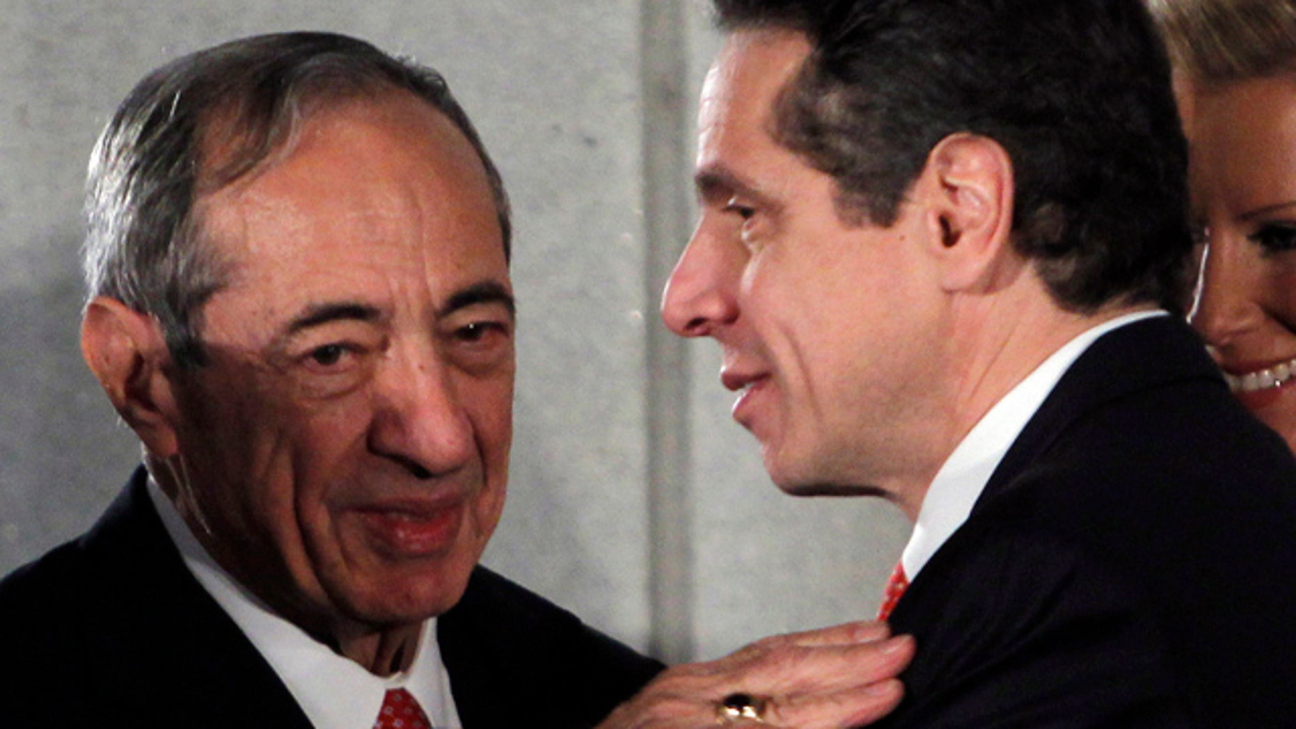 FILE- In this Jan. 1, 2011 file photo, former New York Gov. Mario Cuomo, left, talks with his son and current New York Gov. Andrew Cuomo, during a swearing-in ceremony in the War Room at the Capitol in Albany, N.Y.  (AP Photo/Mike Groll, Pool)