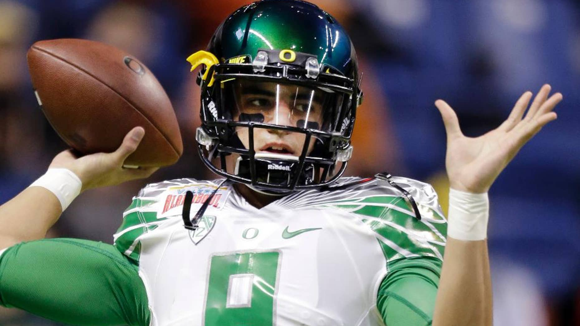 FILE - This Dec. 30, 2013, file photo shows Oregon's Marcus Mariota warms up for the Valero Alamo Bowl NCAA college football game against Texas in San Antonio. Mariota hears the jokes about his course load this semester: yoga and golf. For those who suggest he might want to add an elective in underwater basketweaving, the reality is this: The star quarterback for No. 3 Oregon finished his degree requirements in just three years.  (AP Photo/Eric Gay, File)