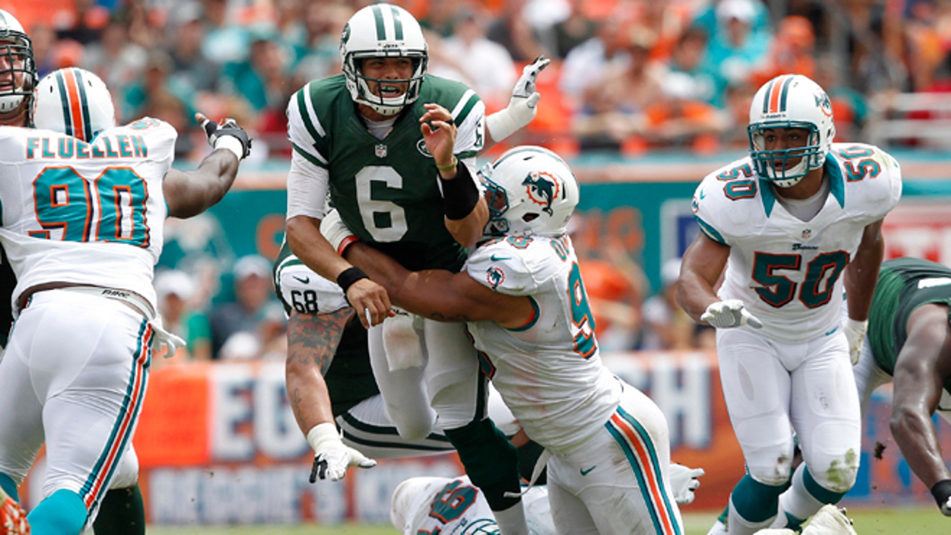 MIAMI GARDENS, FL - SEPTEMBER 23: Jared Odrick #98 of the Miami Dolphins hits Mark Sanchez #6 of the New York Jets as he gets the ball away on September 23, 2012 at Sun Life Stadium in Miami Gardens, Florida. (Photo by Joel Auerbach/Getty Images)