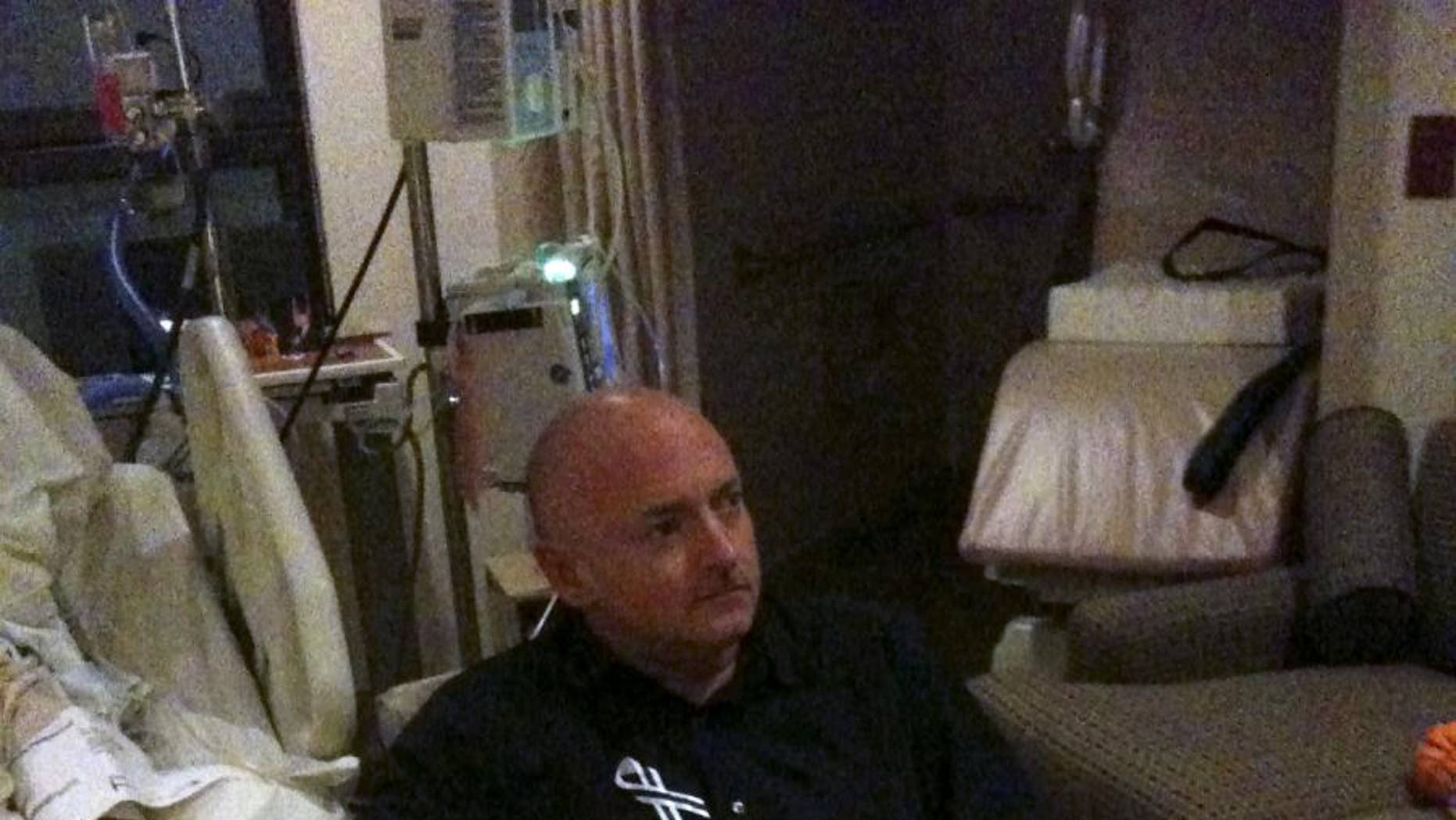 This photo provided by the office of U.S. Rep. Gabrielle Giffords shows Mark Kelly watching the State of the Union address with Giffords in her hospital room in Houston, Tuesday, Jan. 25, 2011. (AP Photo/Office of U.S. Rep. Gabrielle Giffords)